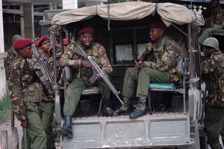 wpid-kenya-soldiers-stand-by-as-hundreds-of-people-attend-the-funeral-ceremony-for-moderate-muslim-cleric-mohamed-idris-shot-dead-by-unidentified-gunmen-on-june-10-2014-in-the-kenyan-port-city-of-mombasa.jpg