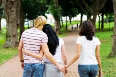 Man holding another woman's hands behind his girlfriends back
